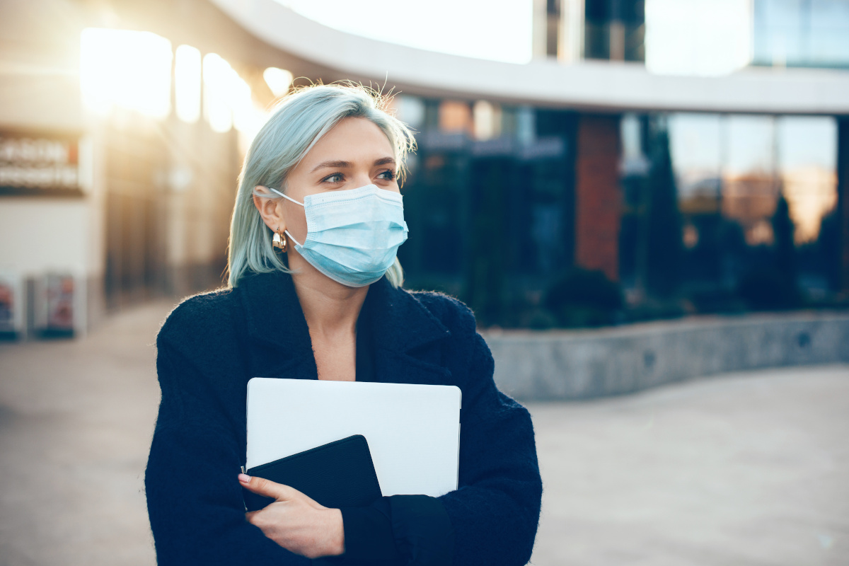Careful caucasian businesswoman holding a laptop and tablet while wearing a protective mask