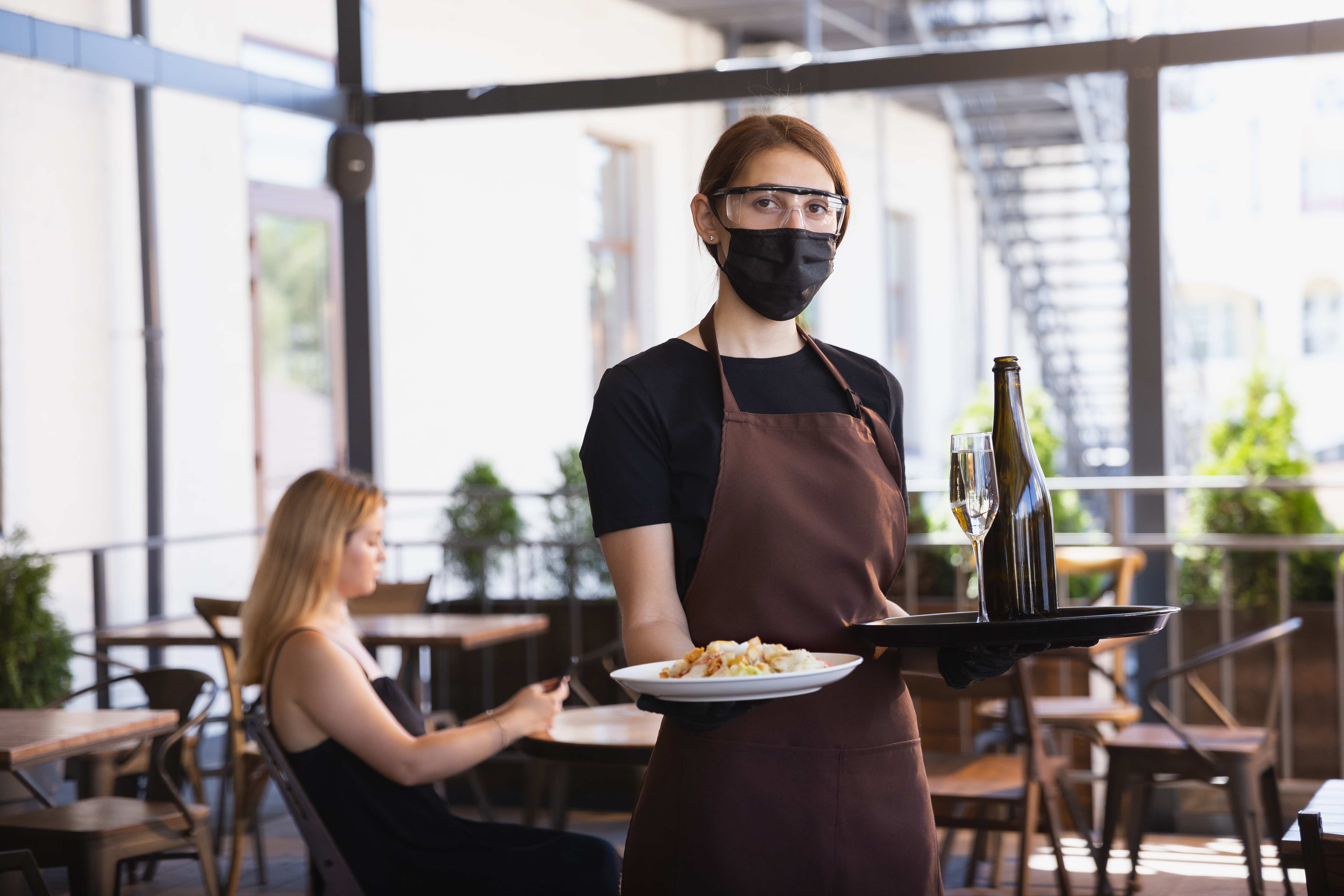 The waitress works in a restaurant in a medical mask, gloves during coronavirus pandemic