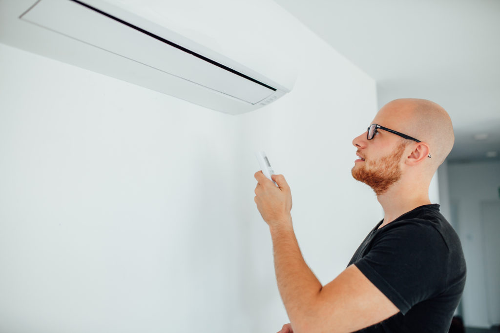 Man is turning on ductless air condition by remote control