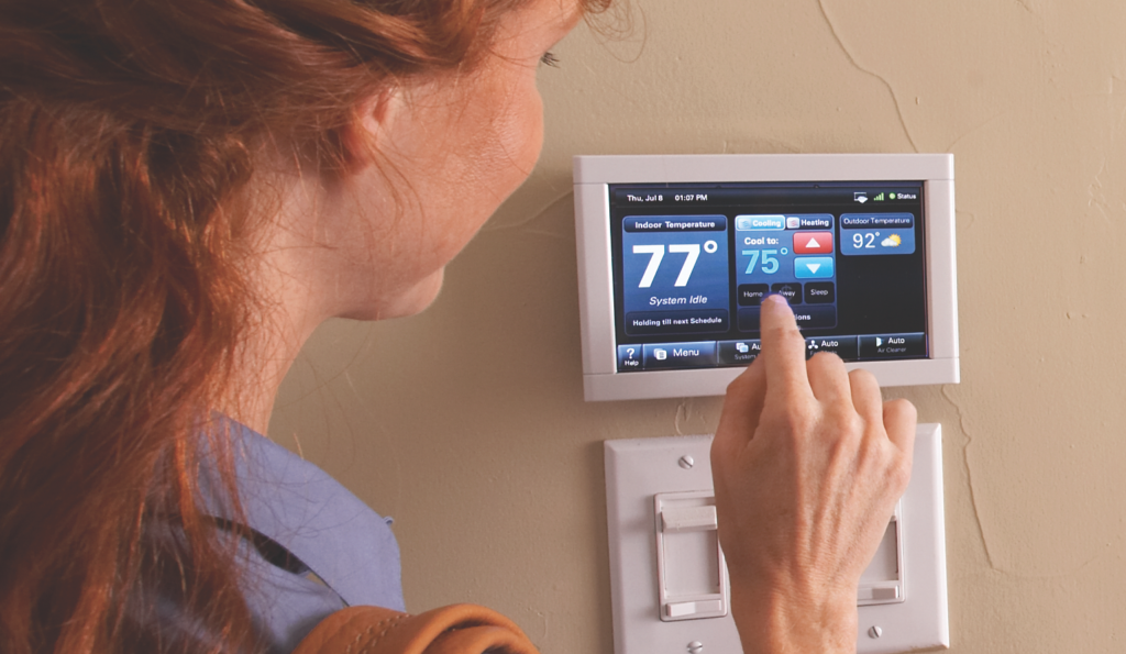 Woman using smart thermostat