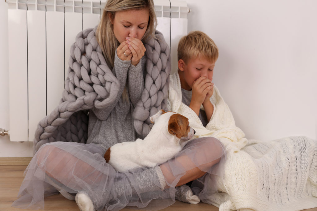 Mom and son keeping warm under a blanket near a furnace