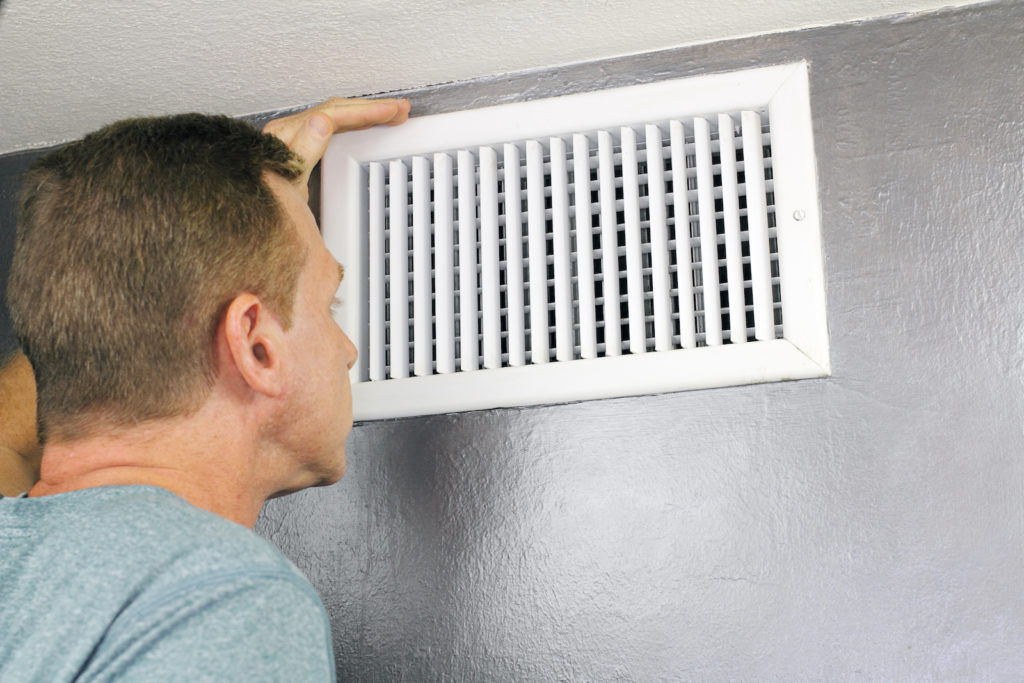 Man smelling air from heat vent