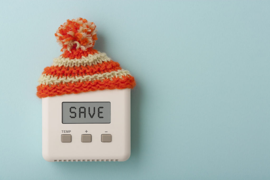 The word SAVE on a digital room thermostat wearing wooly hat