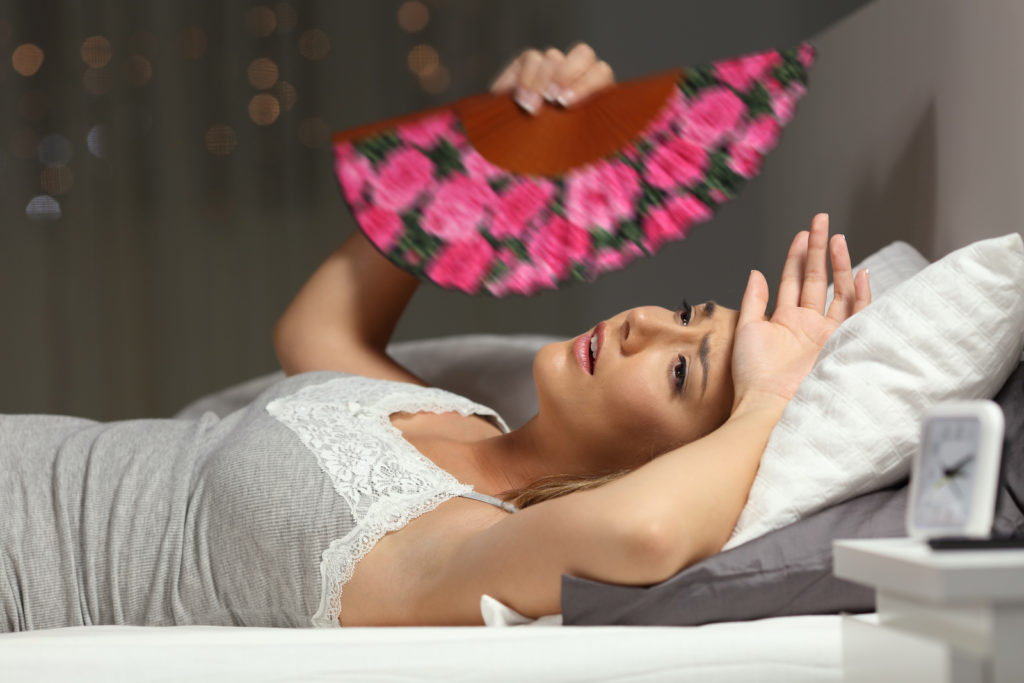 Woman in bed fanning herself to keep cool